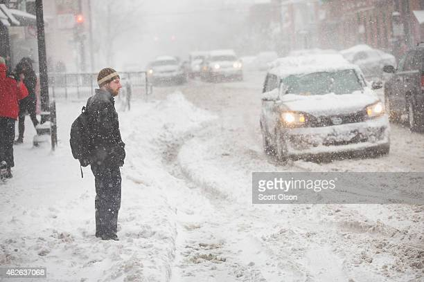 A man waits for a ride along a snowcovered street on February 1 2015 in Chicago Illinois Fifteen inches or more of snow is expected to fall on the...