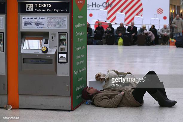 A man waits for a train in Waterloo Station as severe weather has caused delays and cancellations to numerous UK rail services on December 24 2013 in...