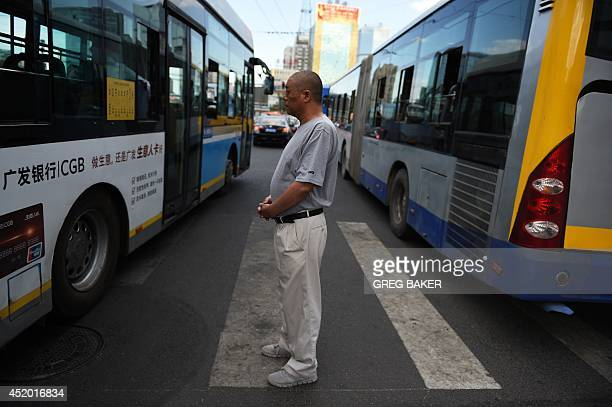 A man waits for buses to pass at a pedestrian crossing in a busy intersection in Beijing on July 11 2014 Both drivers and pedestrians commonly ignore...