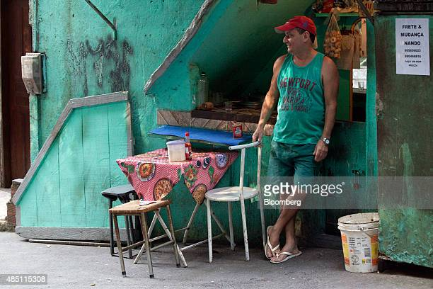 A man waits for customers at a small food stand and bar in the Rocinha favela in Rio de Janeiro Brazil on Thursday Aug 20 2015 With joblessness on...