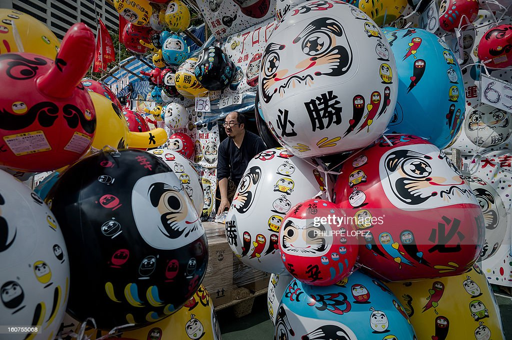 A man waits for customers at a stall selling inflatable figures at a Chinese New Year fair in Hong Kong on February 5, 2013. The Chinese New Year festival falls on February 10, 2013. AFP PHOTO / Philippe Lopez