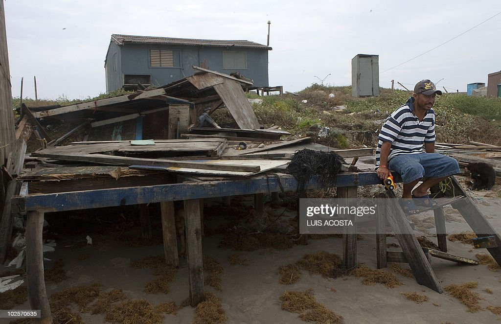 A man waits for help sitting in his damaged house after the passage of Hurricane Alex in Bagdad beach, in Matamoros, Tamaulipas State, on July 1, 2010. Alex, the first hurricane of the Atlantic season, weakened across northeast Mexico as it neared high mountains on Thursday, after disrupting oil clean-up operations in the Gulf of Mexico. Alex was downgraded to a tropical storm after roaring ashore late Wednesday as a Category Two hurricane slightly south of the eastern US-Mexico border. AFP PHOTO/Luis Acosta