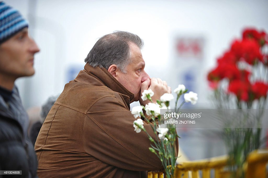 A man waits for news at the scene where the Maxima supermarket roof collapsed in Riga on November 22, 2013. Thirty three were killed and around 40 others injured when the roof of a supermarket collapsed a day earlier in a suburb of Latvia's capital Riga, emergency services said.