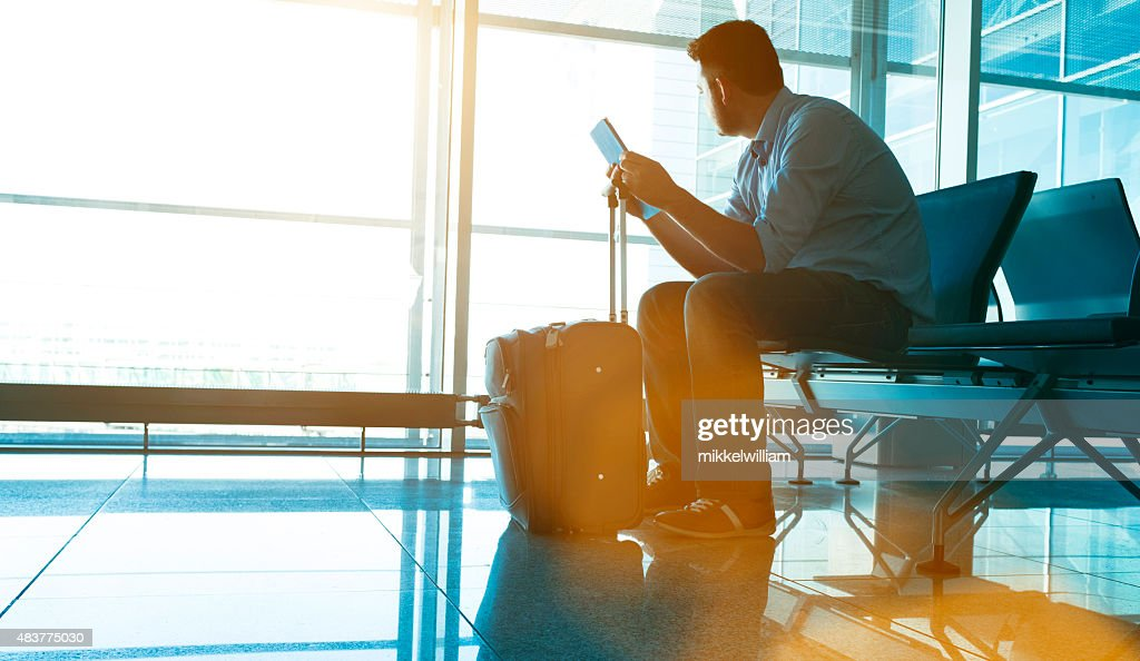 Man waits for plane at airport and looks for flight : Stock Photo