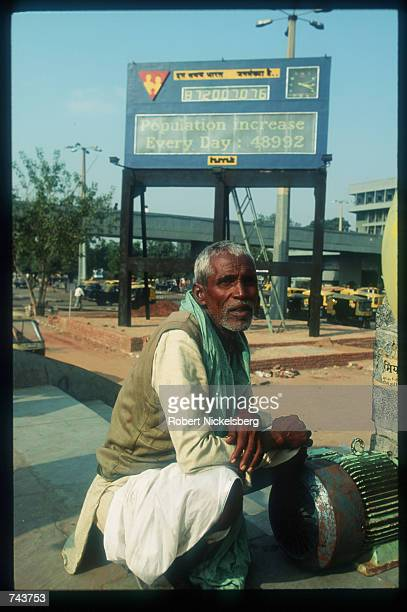 A man waits near the population clock near the main bus terminal June 10 1992 in Delhi India India is one of the world's most populous countries with...