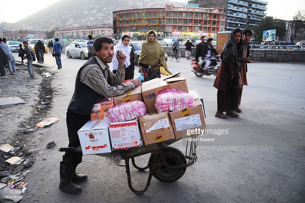 A man waits on the roadside at dusk with goods piled up on his push cart on October 15, 2011 in Kabul, Afghanistan.
