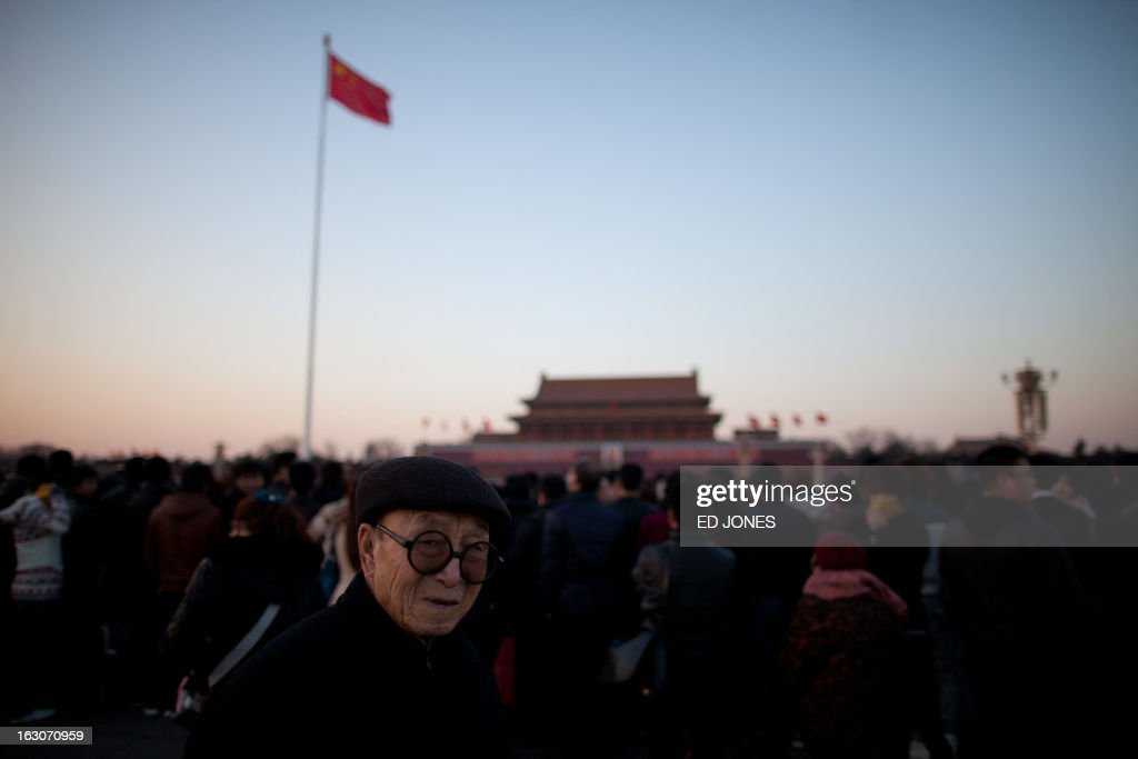 A man waits on Tiananmen Square for the daily flag-lowering ceremony in Beijing on March 4, 2013. Thousands of delegates from across China meet this week to seal a power transfer to new leaders whose first months running the Communist Party have pumped up expectations with a deluge of propaganda. AFP PHOTO / Ed Jones