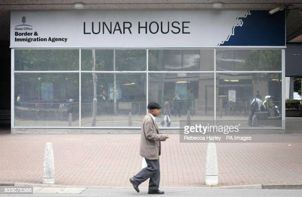 A man waits outside Lunar House the Home Office Border and Immigration Agency West Croydon London