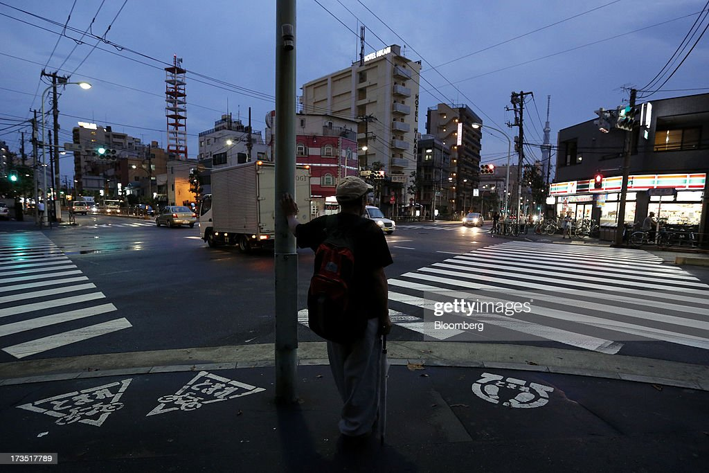 A man waits to cross a street at night in Tokyo, Japan, on Monday, July 8, 2013. The number of Japanese seniors living alone will rise 54 percent to 7.17 million in 2030 from 4.66 million in 2010, according to the National Institute of Population and Social Security Research, set up by the Ministry of Health, Labour and Welfare. To manage the costs stemming from the aging society, the government aims to push back the pension age to 65 from 60 in stages through 2025. Photographer: Kiyoshi Ota/Bloomberg via Getty Images