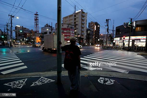 A man waits to cross a street at night in Tokyo Japan on Monday July 8 2013 The number of Japanese seniors living alone will rise 54 percent to 717...