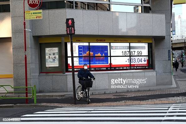 A man waits to cross the street next to an electric quotation board flashing numbers of the Nikkei key index of the Tokyo Stock Exchange in Tokyo on...