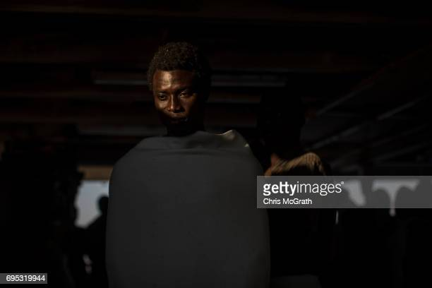 A man waits to disembark the Migrant Offshore Aid Station Phoenix vessel after arriving in port on June 12 2017 in Reggio Calabria Italy An estimated...