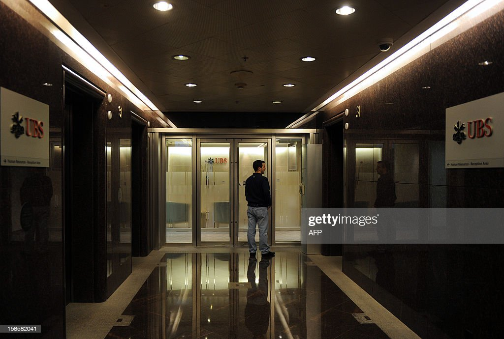 A man waits to enter an office of Swiss banking giant UBS in Hong Kong on December 20, 2012. Hong Kong's de facto central bank said on December 20 it would probe Swiss banking giant UBS over possible rigging of the city's interbank offered rate, a day after the bank agreed to pay a huge fine over the Libor scandal. AFP PHOTO / Dale de la Rey