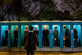 A man waits to use a row of portable toilets during 'Hanami' or Flowerviewing parties under cherry blossom trees in full bloom in Ueno Park on April...