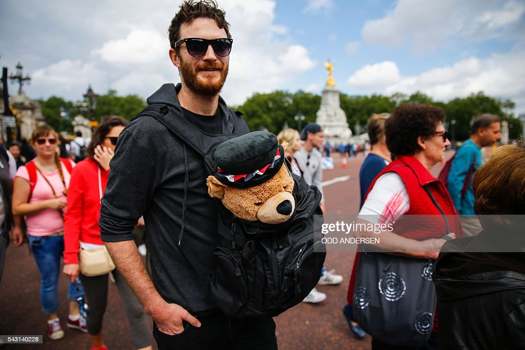 A man waits with a soft toy bear for the Changing of the Guard ceremony outside Buckingham Palace in central London on June 26, 2016. Britain's opposition Labour party plunged into turmoil Sunday and the prospect of Scottish independence drew closer, ahead of a showdown with EU leaders over the country's seismic vote to leave the bloc. Two days after Prime Minister David Cameron resigned over his failure to keep Britain in the European Union, Labour leader Jeremy Corbyn faced a revolt by his lawmakers who called for him, too, to quit. / AFP / Odd ANDERSEN