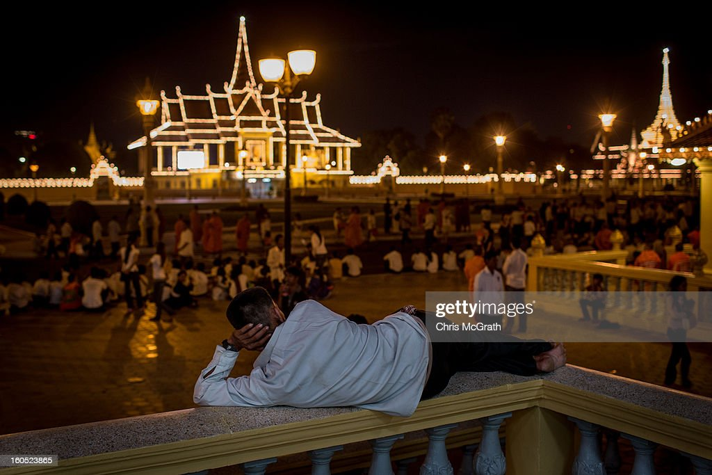A man waits with hundreds of mourners outside the Royal Palace for a ceremony involving King Norodom Sihamoni to finish before police let them onto the grounds to pay their respects to former King Norodom Sihanouk on February 2, 2013 in Phnom Penh, Cambodia. The former kings coffin was transported to the cremation site yesterday after being paraded through the capital in a lavish funeral procession. The cremation will take place on Monday the 4th of February, the funeral pyre will be lit by his wife and son King Norodom Sihamoni.
