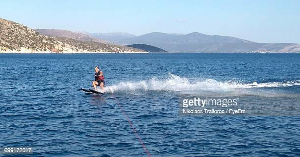Man Wakeboarding In Sea Against Mountains