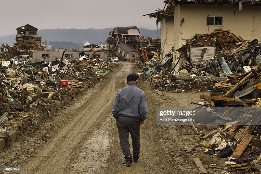 A man walk among debris at Rikuzentakata on March 26, 2011 in Iwate Prefecture, Japan. The 9.0 magnitude strong earthquake struck offshore on March 11 at 2:46pm local time, triggering a tsunami wave of up to ten metres which engulfed large parts of north-eastern Japan, and also damaging the Fukushima nuclear plant and threatening a nuclear catastrophe. The death toll continues to rise with numbers of dead and missing exceeding 20,000 in a tragedy not seen since World War II in Japan.