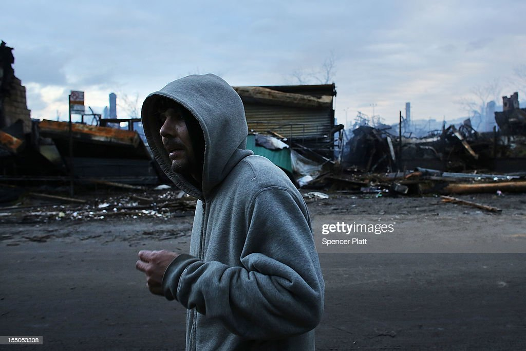 A man walk by homes and businesses destroyed by fire during Hurricane Sandy in the Rockaway neighborhood on October 31, 2012 in the Queens borough of New York City. With the death toll currently at 55 and millions of homes and businesses without power, the US east coast is attempting to recover from the affects of floods, fires and power outages brought on by Hurricane Sandy. JFK airport in New York and Newark airport in New Jersey expect to resume flights on Wednesday morning and the New York Stock Exchange commenced trading after being closed for two days.
