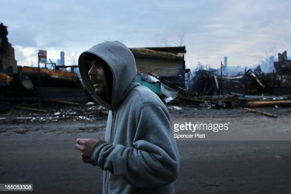 A man walk by homes and businesses destroyed by fire during Hurricane Sandy in the Rockaway neighborhood on October 31 2012 in the Queens borough of...