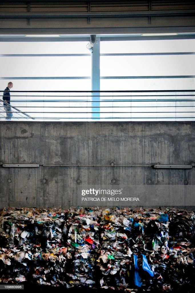 A man walk past piles plastic waste for recycling at Valorsul a waste treatment plant in Lisbon on January 22, 2013.