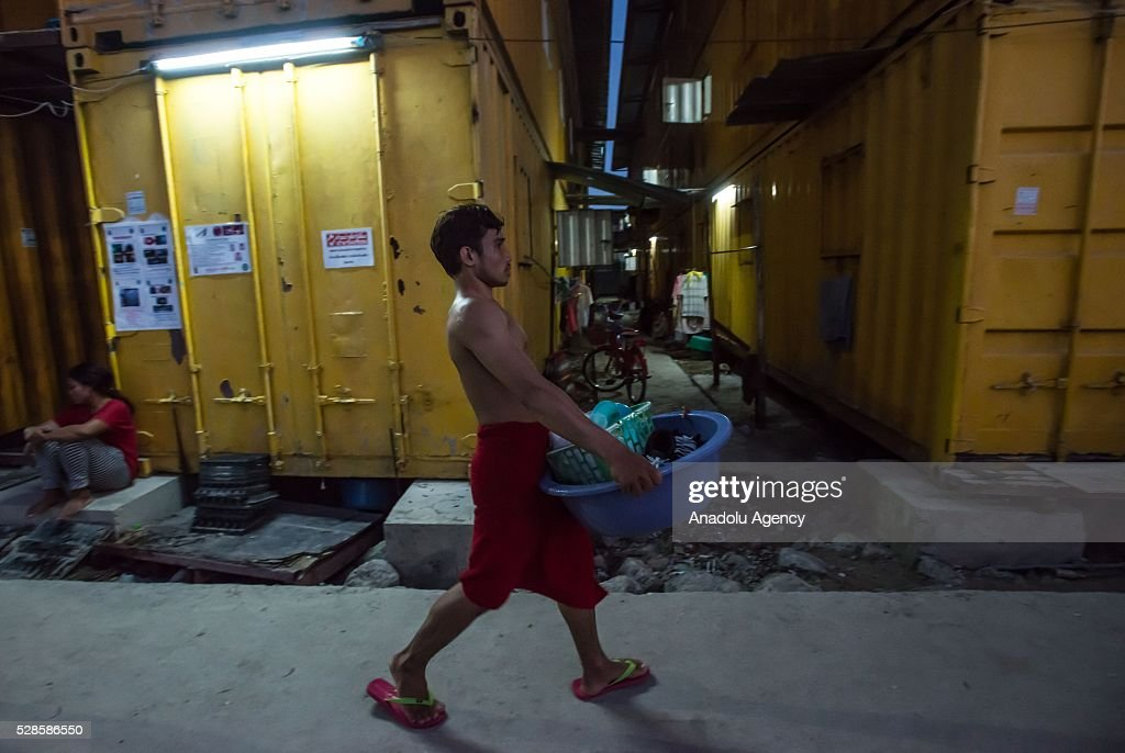 A man walk past steel containers after take a shower at a construction workers' camp on May 6, 2016 in Bangkok, Thailand. Mainly migrants from neighboring countries, like Cambodia and Laos, live in this camp, which has grocery shops, a common washing area and even a small school, on the outskirts of Bangkok.