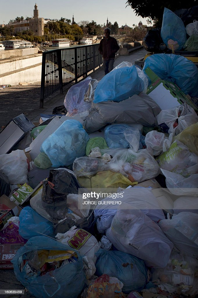 A man walk past uncollected rubbish in a street of Sevilla on February 4, 2013. Rubbish collectors have been on strike in the municipality of Sevilla to protest against the austerity cuts imposed by the town hall.