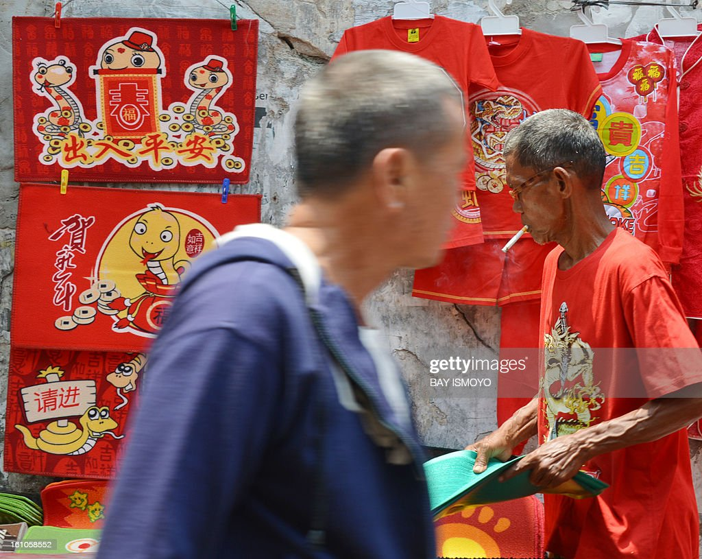 A man walk spast a sidewalk vendor selling t-shirt with snake designs on it for Chinese Lunar New Year in the Indonesian capital city of Jakarta on February 9, 2013 the country's minority Chinese-Indonesians prepare to celebrate the Chinese New Year. The Year of the Snake falls across the region on February 10. AFP PHOTO / Bay ISMOYO