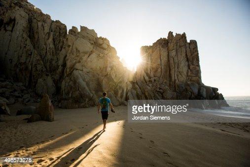 A man walking a beach at sunrise.
