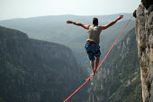 Man walking a 60 mt. slackline placed over the Verdon Gorges in France.