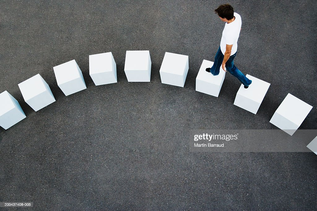 Man walking across line of giant white cubes, elevated view