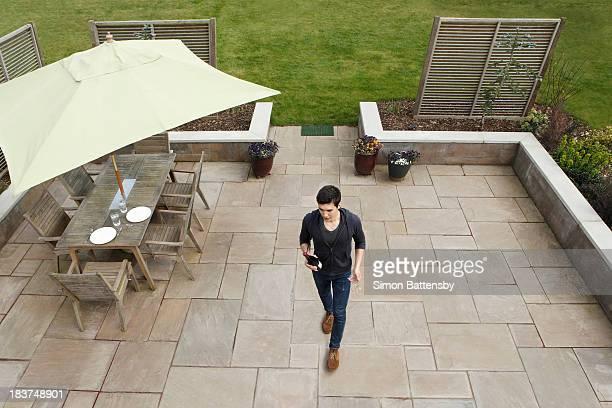 Man walking across patio with wine bottle