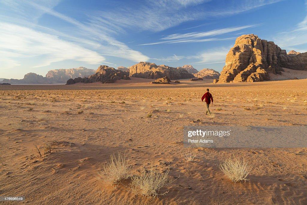 Man walking across the desert, Wadi Rum, Jordan