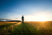 Lonely man walking along a trail through a green meadow at sunset
