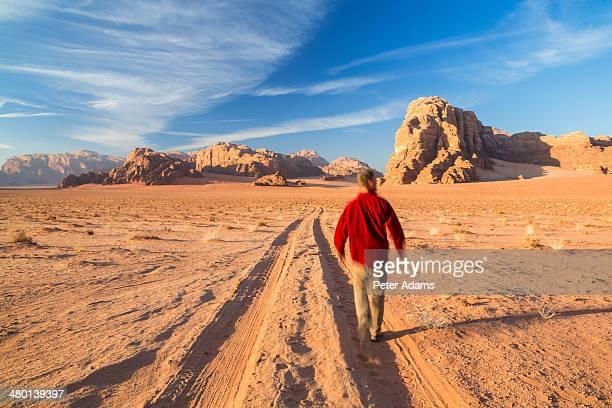 Man walking alone on tracks in Wadi Rum desert
