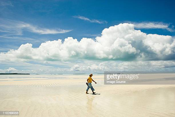 Man walking along beach