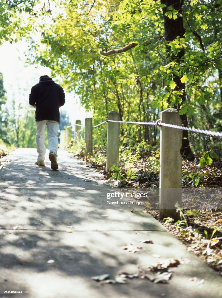 Man Walking Along Cement Path in Park, Rear View