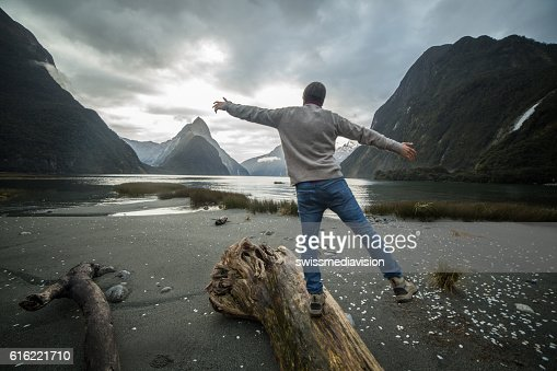 Man walking along log in mountains, rear view : Stock-Foto