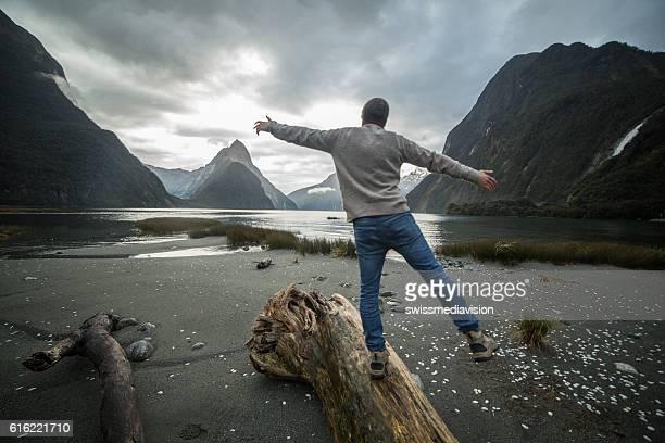 Man walking along log in mountains, rear view
