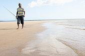 Man Walking Along Shore Of Beach Carrying Fishing Rod
