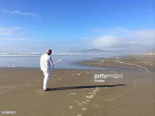 Man walking along the beach, Cannon Beach, Oregon