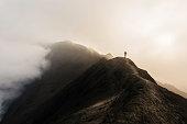 man walking along volcano crater