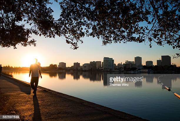 Man walking at sunset along lake