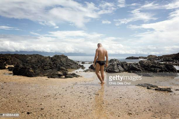 Man walking at the beach with white cloudy sky