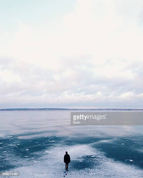 Man walking away across frozen lake