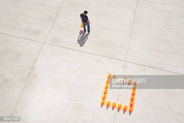 Man walking away from box of traffic cones with one