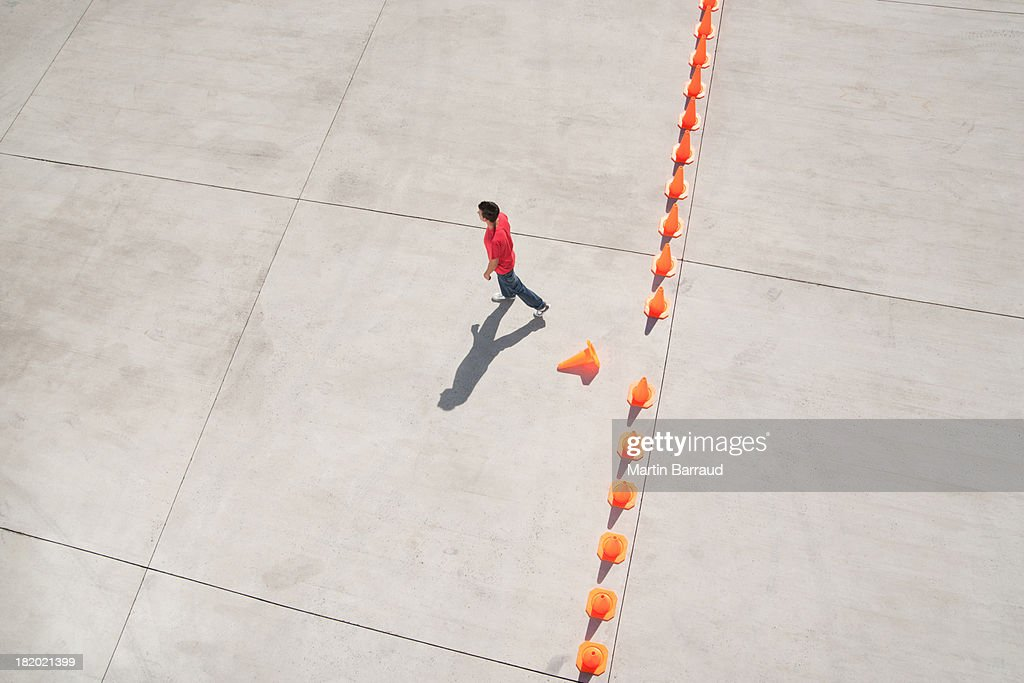 Man walking away from row of traffic cones with one misplaced : Stock Photo