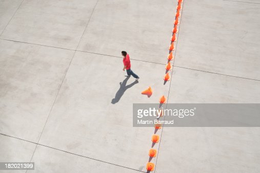 Man walking away from row of traffic cones with one misplaced