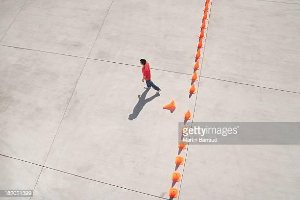 Homem a andar longe da linha de cones de trânsito com um