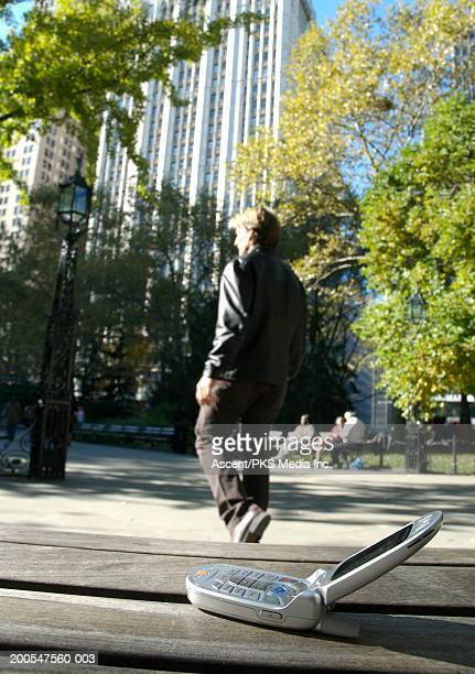 Man walking away, mobile phone lying on park bench